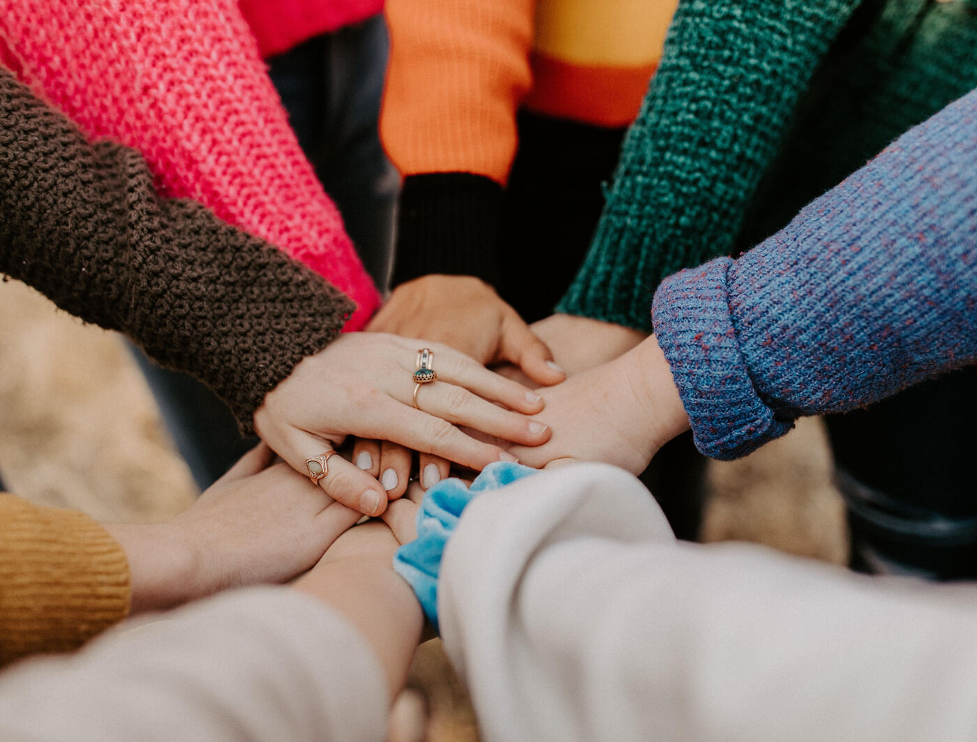 support circle of women hands on top of each other in solidarity